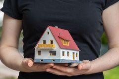 Real estate agent is holding small house in hand Stock Photography