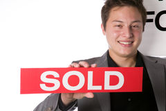 Real estate agent holding a Sold sign Royalty Free Stock Photography