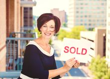 Real estate agent holding sold sign  on city background Royalty Free Stock Photo