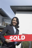 Real Estate Agent Holding Sold Sign Outside House. Portrait of a smiling female real estate agent holding sold sign outside house Stock Photo