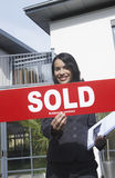 Real Estate Agent Holding Sold Sign Outside House. Portrait of a smiling female real estate agent holding sold sign outside house Royalty Free Stock Photos