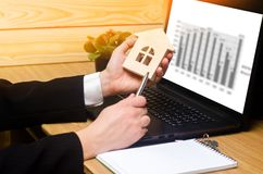 Real estate agent holds a house model, signs  fills documents si Royalty Free Stock Photos