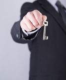 Real estate agent holds out a key Stock Photography