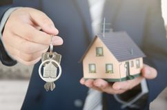 Real estate agent with home keys and house miniature. Realestate key apartment real estate home house homeowner concept royalty free stock photography