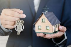 Real estate agent with home keys and house miniature. Realestate key apartment real estate home house homeowner concept royalty free stock images