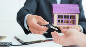 Real estate agent in suit holds house model in one hand and in the second hand holds out the keys of the house to woman. stock images