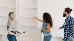 Real estate agent house modern interior design. Real estate agent discussing with clients house modern interior design. Young couple enthusiastic about new home stock video