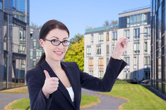 Real estate agent with key standing on street against modern bui Royalty Free Stock Photo