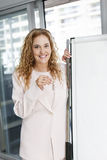 Real estate agent with keys and flip chart Royalty Free Stock Photo