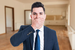 Real estate agent looking perplexed. Or scared of something and holding hand on mouth Royalty Free Stock Photos
