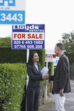 Real Estate Agent And Man Shaking Hands By Sale Signs Royalty Free Stock Photos