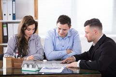 Real Estate Agent Meeting With Couple. Couple Planning New House Project With Architect At Office Royalty Free Stock Image