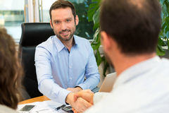 Real estate agent meeting couple at the office Stock Images