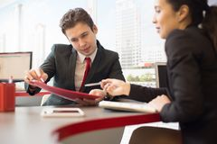 Real Estate Agent in Meeting. Portrait of two business people discussing marketing statistics pointing at documents during meeting in modern office Royalty Free Stock Photo