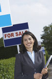 Real estate agent near for sale signs portrait Royalty Free Stock Photo