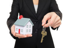 Real estate agent new house keys concept. Realtor showing holding house keys and mini house model. Buying new home conceptual image with business woman in suit