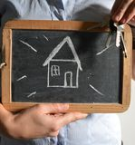 Simple new house / keys concept. Blackboard with a childlike drawing of a new house, drawn on a blackboard Stock Photography