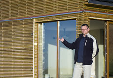 Real estate agent offer. A man standing in front of a wooden elevation house, making an offer Royalty Free Stock Photos