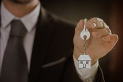 Real Estate agent offering house key. Buy new house concept Royalty Free Stock Photos