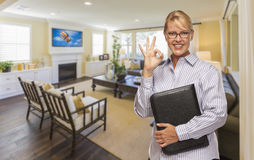 Real Estate Agent with Okay Sign in a Living Room. Smiling Real Estate Agent with Okay Sign in Living Room of New House Stock Photography