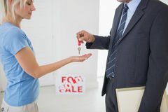 Real estate agent passing house key to woman Royalty Free Stock Photo