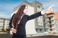Real estate agent pointing at something. Real estate agent looking and pointing finger at something outside in front of building stock photography