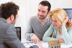 Real estate agent present project on blueprint to a young couple Stock Photography