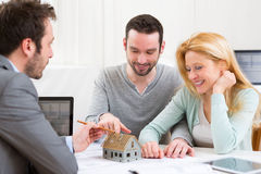 Real estate agent present project on miniature house to a young. View of a Real estate agent present project on miniature house to a young couple Royalty Free Stock Images