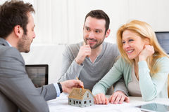 Real estate agent present project on miniature house to a young Royalty Free Stock Image