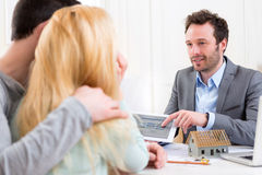 Real estate agent present project on tablet to a young couple Stock Photography