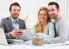 Real estate agent present project on tablet to a young couple Royalty Free Stock Photo