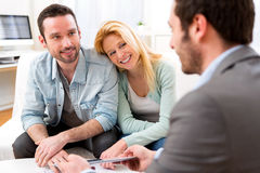 Real estate agent present project on tablet to a young couple Stock Image