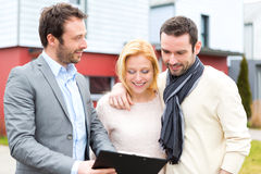 Real estate agent presenting contract to young couple Royalty Free Stock Image