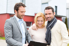 Real estate agent presenting contract to young couple Stock Photos
