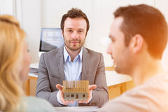 Real estate agent presents miniature house to a young couple Stock Images