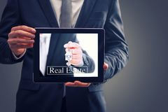 Real Estate Agent. Man Showing Keys On Tablet Stock Photography