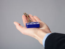 Real estate agent's hand holding a key. From a house, closeup shot Royalty Free Stock Photos