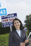 Real Estate Agent By For Sale Sign Outside House. Portrait of a happy and confident female real estate agent standing by for sale sign outside house Royalty Free Stock Photos