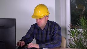 Real estate agent sales man with helmet working with computer at desk in office. Real estate agent sales man with helmet sign documents at desk in office. Static stock footage