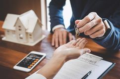 Free Real Estate Agent Sales Manager Holding Filing Keys To Customer Royalty Free Stock Photo - 123927125