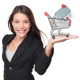 Real estate agent selling home holding mini house. In shopping cart. Female realtor in business suit showing model house smiling happy isolated on white Stock Images
