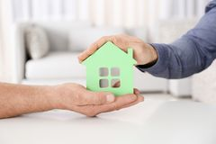 Real estate agent and senior man holding house model. Indoors Stock Photography
