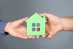 Real estate agent and senior man holding house model. On grey background stock image