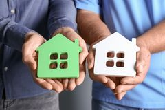 Real estate agent and senior man holding house models. Closeup Royalty Free Stock Photo