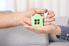 Real estate agent with senior man holding house. Model and key indoors Royalty Free Stock Photo