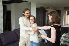 Real estate agent shaking hands couple clients in rental house. Real estate agent holding rental agreement shaking hands to young smiling couple, friendly royalty free stock image