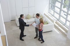 Real Estate Agent Shaking Hands With Man By Woman In New Home. Elevated view of a male real estate agent shaking hands with a men by women in new home stock photography
