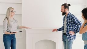 Real estate agent new house modern furniture. Real estate agent showing clients new house with modern furniture. Young couple amazed by light spacious place stock video footage