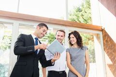 Real-estate agent showing couple new home. Young couple meeting real-estate showing a house project on a digital tablet Royalty Free Stock Images
