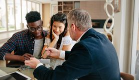 Realtor explaining lease agreement to a couple. Real estate agent showing detail of  lease agreement to interracial couple. Estate broker explaining lease Royalty Free Stock Images